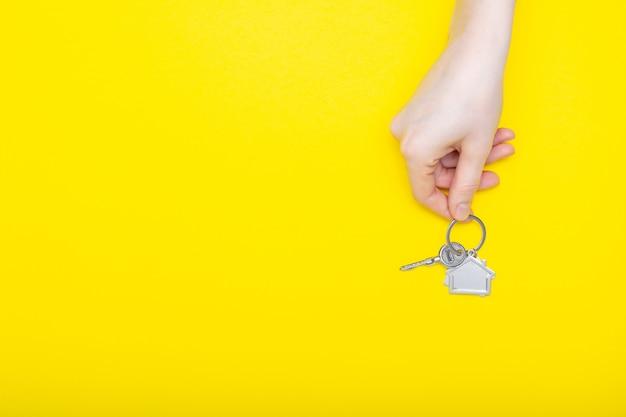 Alloggi le chiavi con il ninnolo in mano femminile sul fondo di colore, vista superiore con lo spazio della copia. chiave di casa su sfondo giallo. stile minimal laico piatto con posto per il testo.
