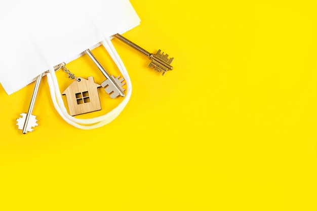 Chiavi di casa su uno sfondo giallo in una confezione regalo di carta bianca.