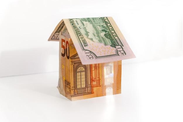 Casa fatta dal concetto di banconote da 50 euro e 50 dollari per i prezzi degli immobili, mutui o finanze domestiche