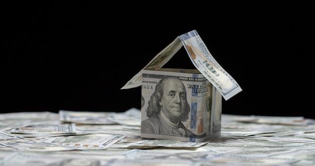 Casa fatta di banconote da cento dollari in piedi su base monetaria americana