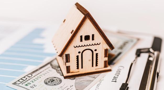 Modello in miniatura della casa e soldi sui documenti. investimenti, immobili, casa, abitazioni