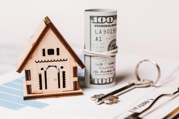 Modello in miniatura della casa e soldi sui documenti. investimenti, immobili, casa, alloggi