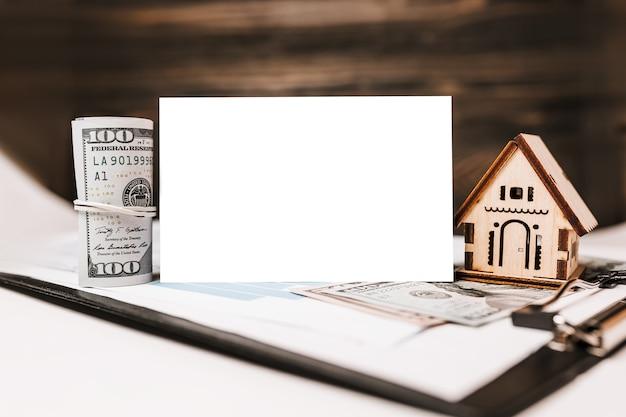Modello in miniatura di casa e soldi con muro bianco sui documenti