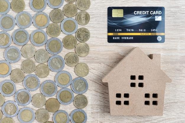 Modello di casa e disposizione delle monete con carta di credito sulla tavola di legno
