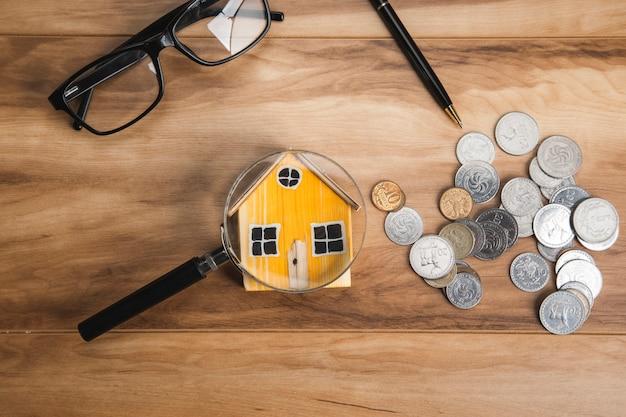 Modello di casa, monete e lente d'ingrandimento sulla tavola di legno
