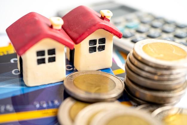 Modello di casa su carta di credito, moneta e calcolatrice, concetto di pagamento rateale.