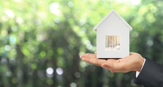 Modello di casa in mano c'è spazio. concetto di casa, alloggio e immobiliare