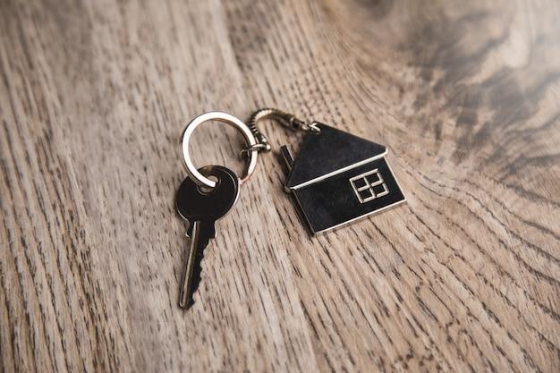 Modello di casa e chiave di casa sul tavolo