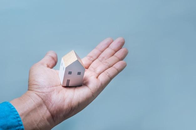Modello di casa sulle mani umane risparmio di denaro, costruzione di edifici, architettura, immobiliare e concetto di proprietà