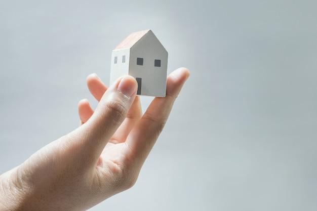 Modello di casa su mani umane