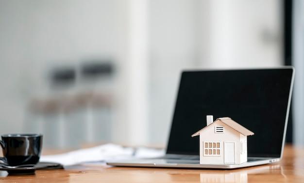 Modello della casa sul computer portatile sulla tavola di legno con lo spazio della copia, concetto del bene immobile.