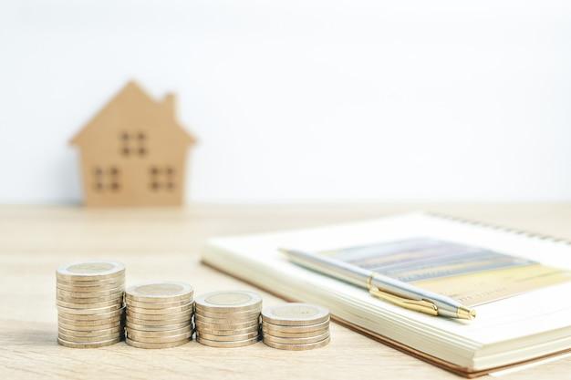 Modello di casa e blocco note con monete sul tavolo per finanza e concetto bancario