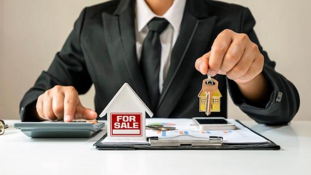 Modello di casa messo su documenti di mutuo per la casa e uomo d'affari che tiene le chiavi di casa concetto finanziario mutuo e immobiliare