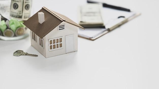 Modello di casa, risparmio di denaro, chiave, accordo sugli appunti e soldi che uniscono sul tavolo bianco.