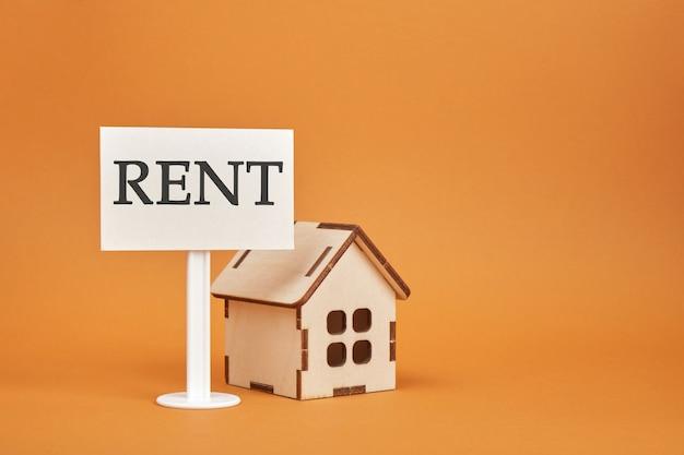 Modello di casa e segno in affitto su uno sfondo marrone copia spazio casa in affitto
