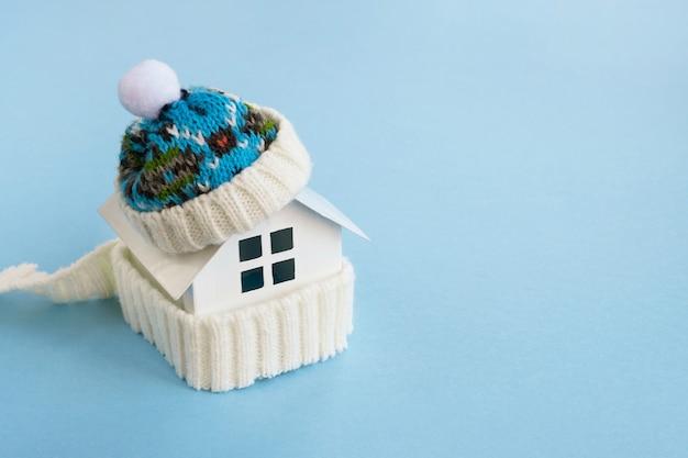 Modello di casa che indossa sciarpa e cappello lavorato a maglia. impianto di riscaldamento, stagione invernale o fredda