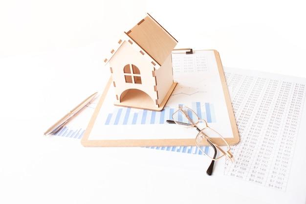 Modello di casa sulla tavola di legno bianca vicino a contratto e bicchieri, concetto di bene immobile
