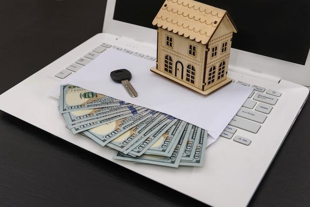 Modello di casa con dollaro in busta e chiave sul computer portatile