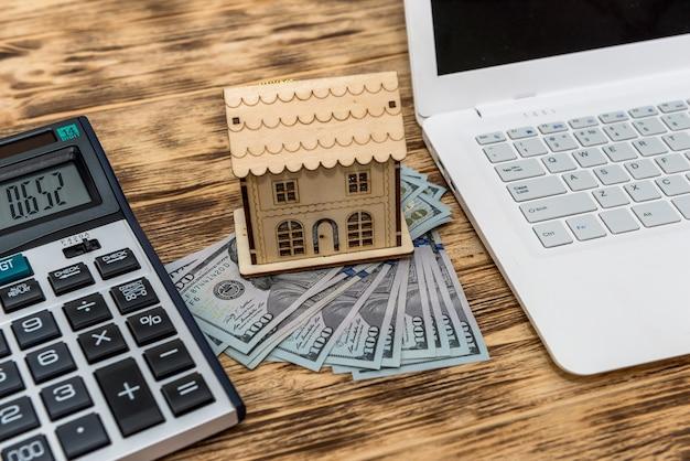 Modello di casa con dollari, laptop e calcolatrice