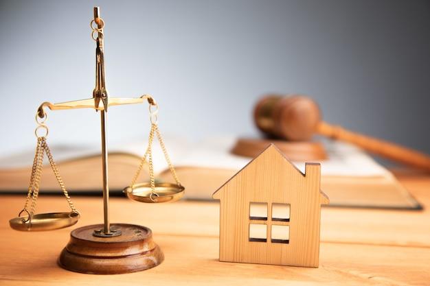 Modello di casa con martelletto, bilancia della giustizia e libro sul tavolo