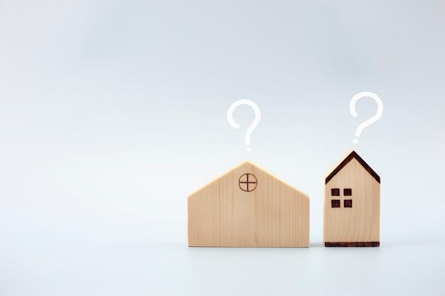 Modello di casa con punti interrogativi su sfondo blu concetto di prestito