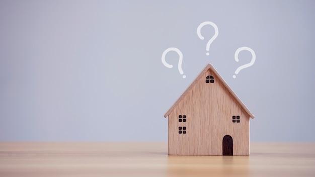 Modello di casa con punti interrogativi sullo sfondo del tavolo che prevede di acquistare proprietà