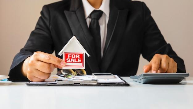 Modello di casa con messaggio in vendita nelle mani delle persone, concetto di prestito. mutui e immobili