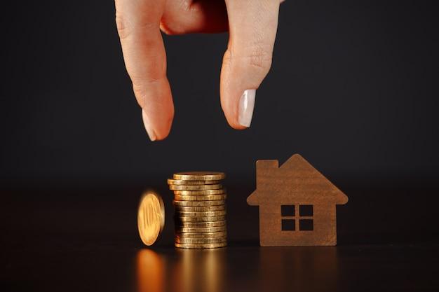 Modello di casa con pila di monete. la mano della donna che tiene fa piani di risparmio per l'alloggio