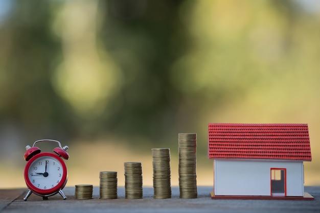 Casa e salvadanaio, orologi, prestiti o risparmi per acquistare una casa e investimenti immobiliari e aziendali in futuro.
