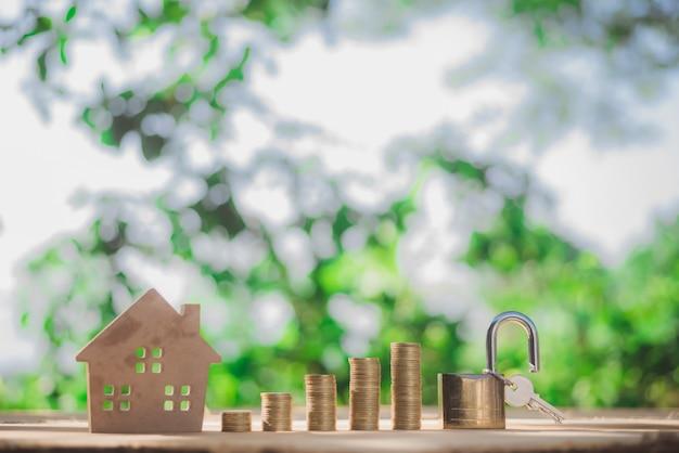 Casa posizionata sulle monete la mano degli uomini sta pianificando risparmi di denaro per comprare un concetto di casa