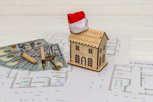 Pianta della casa con modello della casa, dollari e chiave