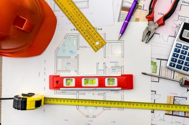 Disegni di progetto di casa con casco, strumenti di muratore su fondo di legno