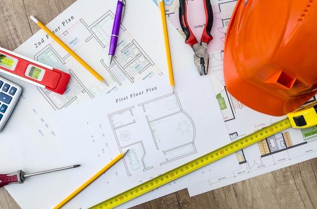 Disegni di progetti di casa con elmo, strumenti da muratore su fondo in legno