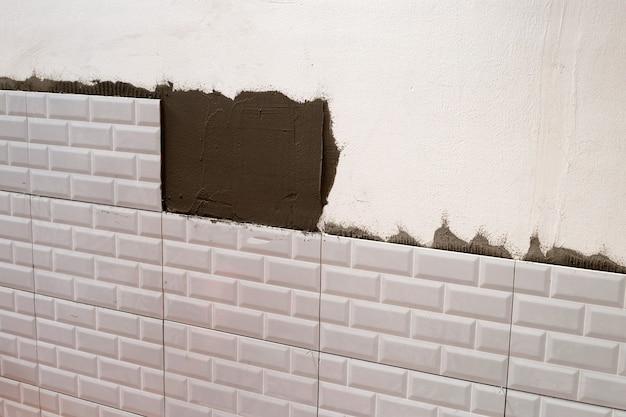Ristrutturazione casa, posa di piastrelle in ceramica sul muro.