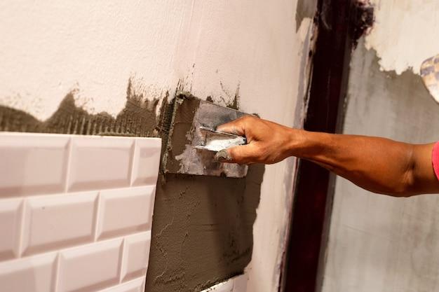 Ristrutturazione casa, posa piastrelle in ceramica sul muro