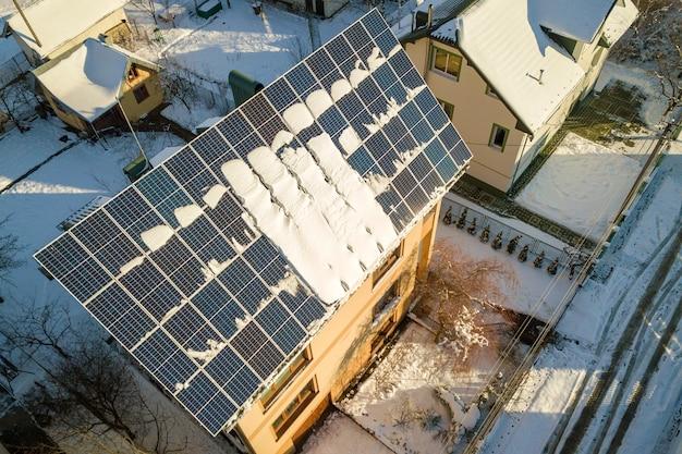 Tetto della casa coperto di pannelli solari in inverno con neve in cima. efficienza energetica e concetto di manutenzione.