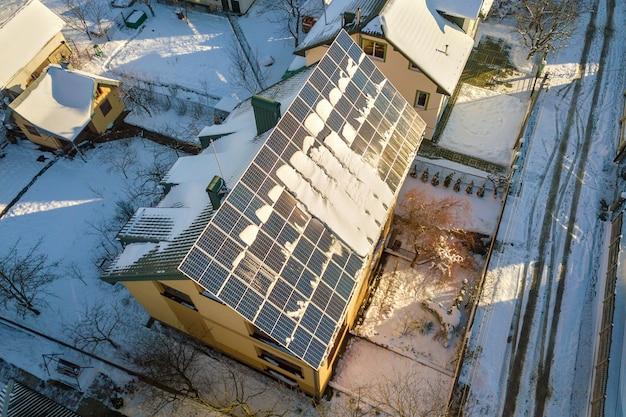 Tetto della casa coperto di pannelli solari in inverno con neve in cima.