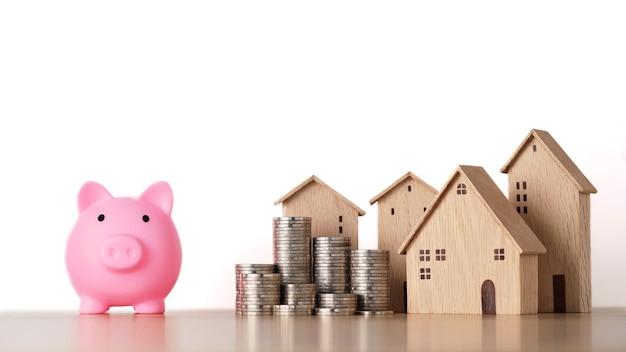 Casa e monete di accatastamento risparmiando crescita con salvadanaio isolato e sfondo bianco