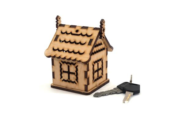 Casa con chiavi. acquisto domestico o concetto di sicurezza, isolato su bianco, primo piano.