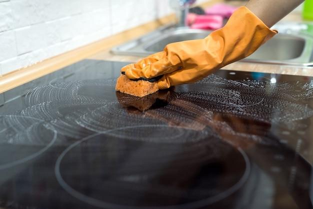Governante che pulisce la superficie della stufa in ceramica moderna con una spugna in cucina