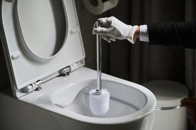 Governante in un pulito grembiule bianco in piedi mentre pulisce una toilette con una spazzola
