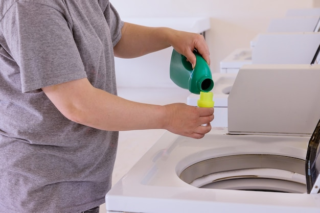 La donna della governante versa la polvere liquida nella lavatrice sulla lavanderia