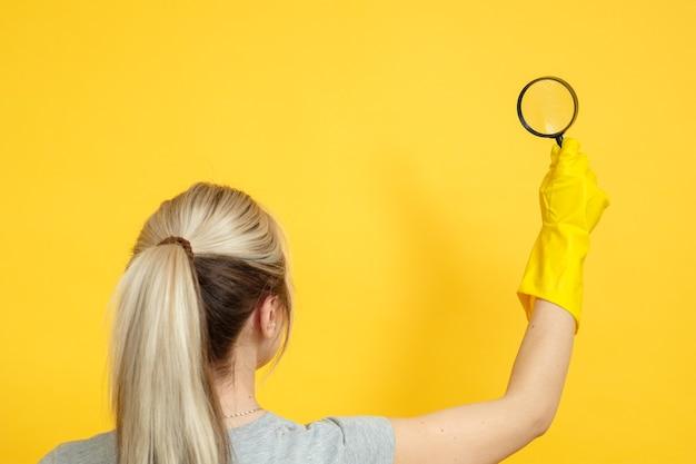 Faccende domestiche. impresa di pulizie. donna con lente d'ingrandimento. consegnare un guanto di gomma