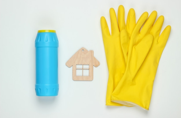 Concetto di pulizie. set di prodotti per la pulizia (guanti, bottiglia per la pulizia) e la figura della casa su priorità bassa bianca. vista dall'alto.