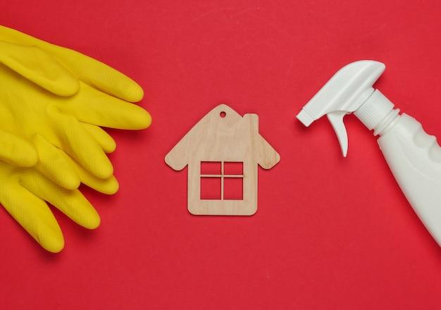 Concetto di pulizie. set di prodotti per la pulizia (guanti, flacone spray) e figura di casa su sfondo rosso. vista dall'alto.