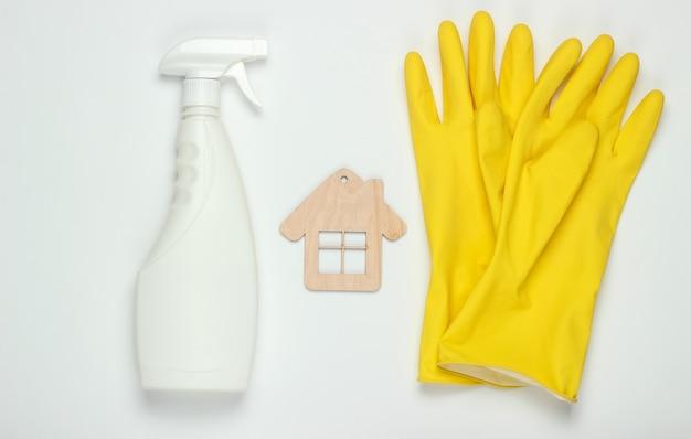 Concetto di pulizie. set di prodotti per la pulizia (guanti, flacone spray) e figura di casa su sfondo bianco. vista dall'alto.