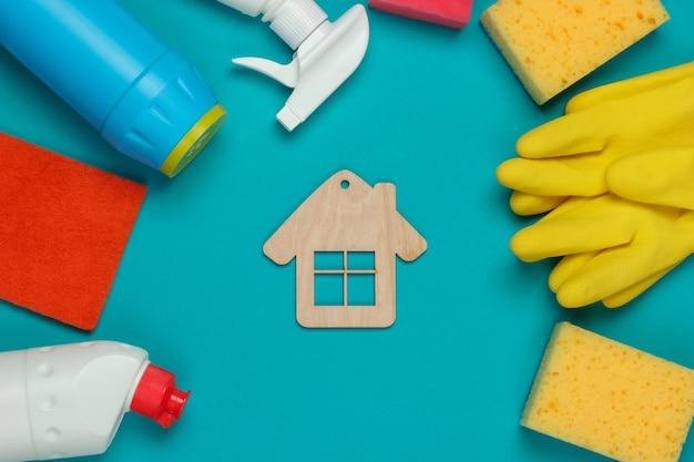 Concetto di pulizie. set di prodotti per la pulizia e la figura della casa su sfondo blu. vista dall'alto.