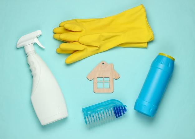 Concetto di pulizie. set di prodotti per la pulizia e la figura della casa su sfondo blu pastello. vista dall'alto.