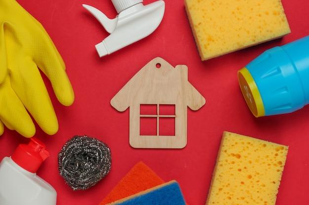 Concetto di pulizie. set di prodotti per la pulizia e la figura della casa su sfondo rosso. vista dall'alto.