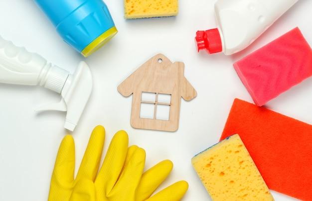 Concetto di pulizie. set di prodotti per la pulizia e la figura della casa su sfondo bianco. vista dall'alto.